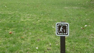 A small brown trail sign in front of a wide area of grass on a trail