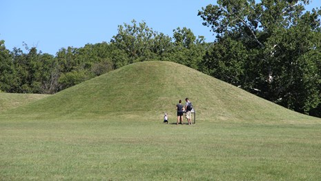 Three people stand in front of a grass-covered mound