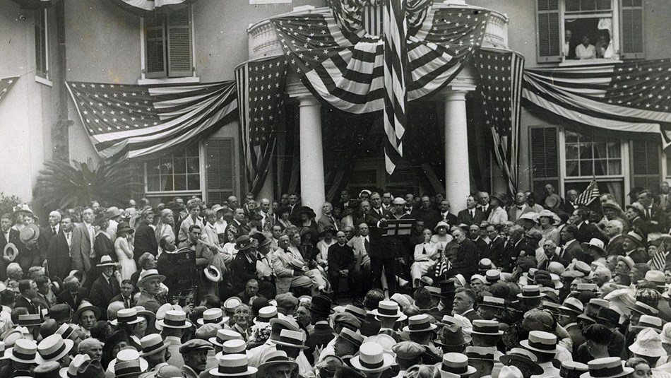 A large group of people crowd around the front of a house draped in American flags.