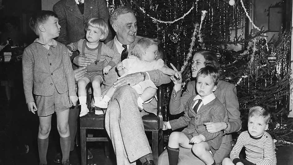 A group of young children gathered around an elder gentleman in front of a Christmas tree.