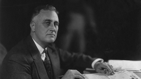 A man wearing a suit sits at a desk with papers in his hand.