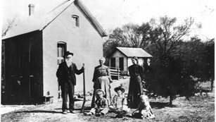 Family posing for a photo in front of their homestead
