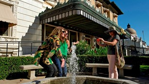 Two women get their photo taken by a fountain in front of the Fordyce Bathhouse.