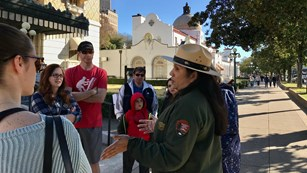A ranger addresses a group of people in front of the Fordyce Bathhouse.
