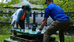 A woman and man work together to lift a large green metal lid off one of the spring boxes.