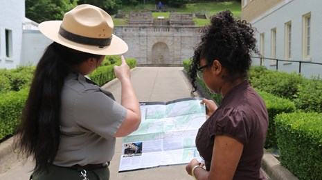 A park ranger uses a park map to provide a visitor with directions