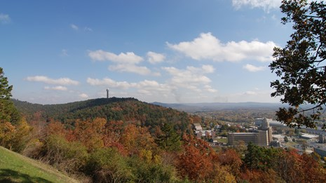 A view from West Mountain overlook looking across rolling hills with fall colored leaves.