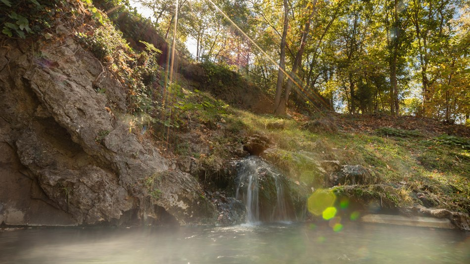 Water cascades over a hillside and into a thermal pool with the sun shining through trees.
