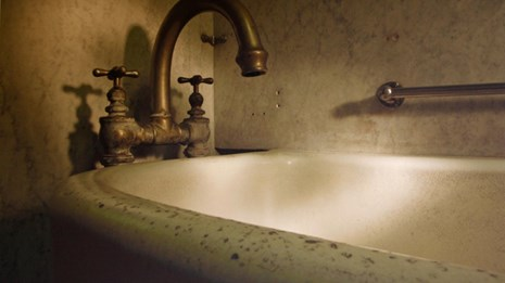 Sepia toned photograph of a historic bathtub in the Fordyce Bathhouse.