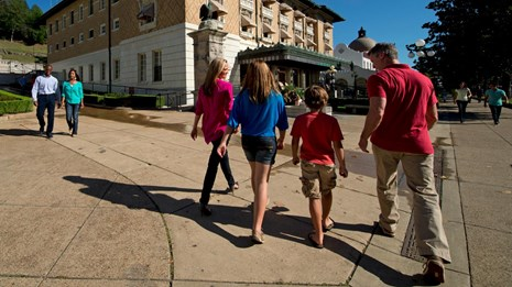 A family strolls down bathhouse row. The Fordyce Bathhouse is in the background.