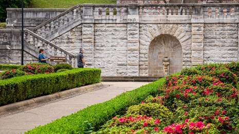 Bright pink azalea bushes line a sidewalk leading up to a large stone staircase with an fountain.