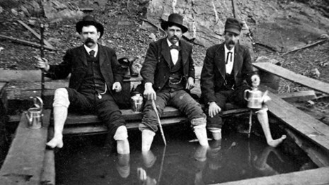 Three men from the mid-1800s are soaking in Corn Hole Spring.