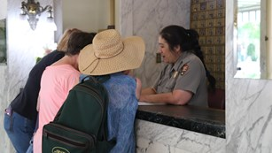 Visitors receive information from a park ranger at the visitor center front desk