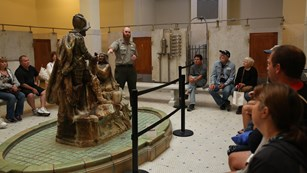 A park ranger speaks to a group of visitors on a tour of the Fordyce Bathhouse
