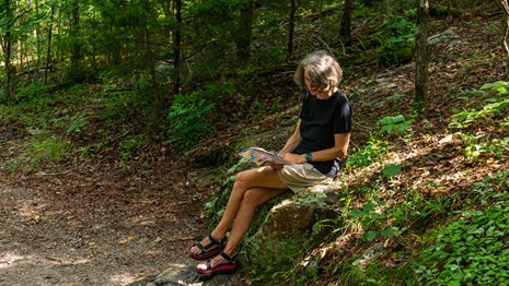 A woman sits on a rock and reading along Hot Springs Mountain