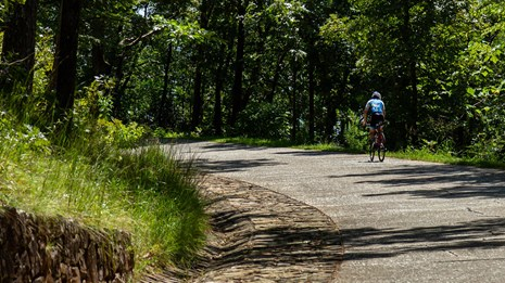 A man biking up the steep road to Hot Springs Mountain