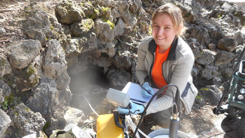 Female scientist is testing the thermal springs water, surrounded by her equipment.
