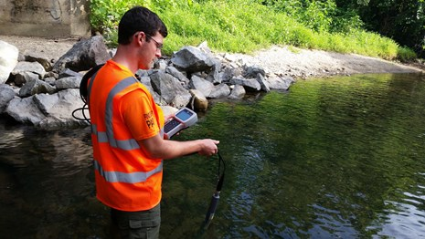 A man dressed in bright orange holds monitoring equipment in a stream.