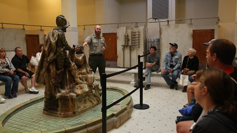 A park ranger speaks to visitors on a guided tour of a historic bathhouse