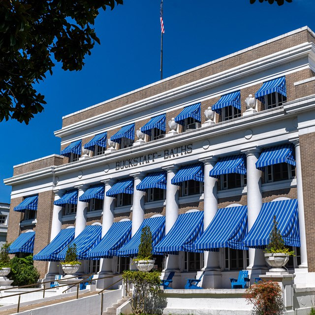 The Buckstaff Bathhouse standing tall featuring its iconic bright blue awnings.