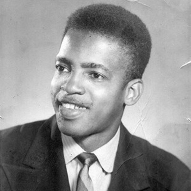 Portait of a young black man, looking slightly to the right and smiling.