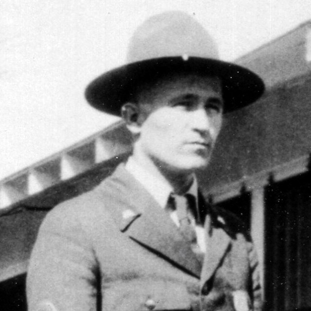 Up close image of a young man dressed in a park ranger uniform, buttoned jacket and flat hat.