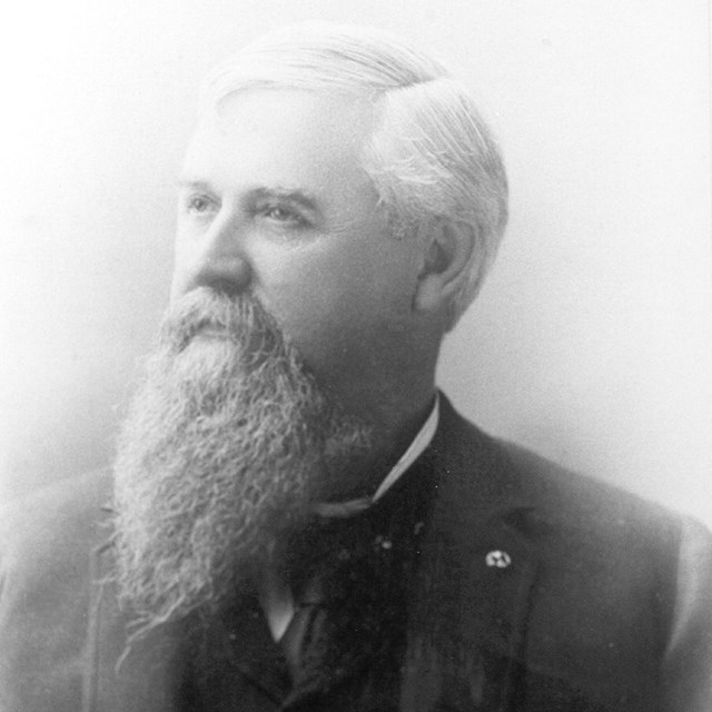 Portrait from 1900s, an elderly gentleman with a long beard looks off in the distance.