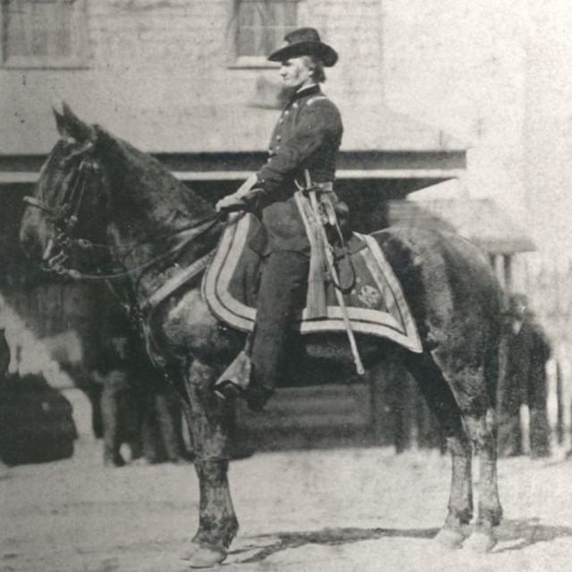 A man wearing a ranger uniform on a large horse, circa late 1800s.