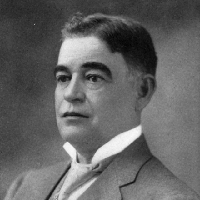 Portrait from late 1800s, a young man in a suit with very defined eyebrows looks off to the side.