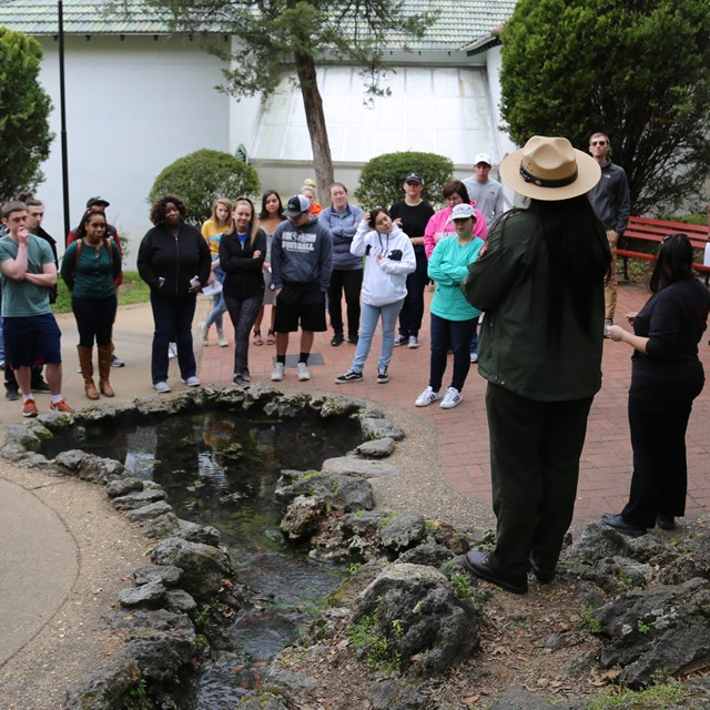 A female ranger delivers a program near one of the thermal springs.
