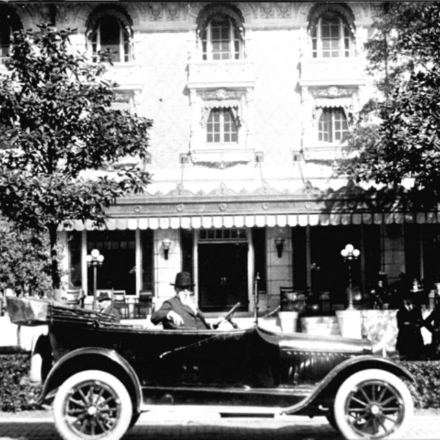 Samuel Fordyce sits in his open air vehicle in front of the Fordyce Bathhouse, circa 1915.