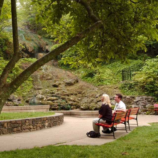A couple sits on a park bench looking at the hot water cascade in the park.