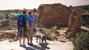 two people with a dog look at a stone structure