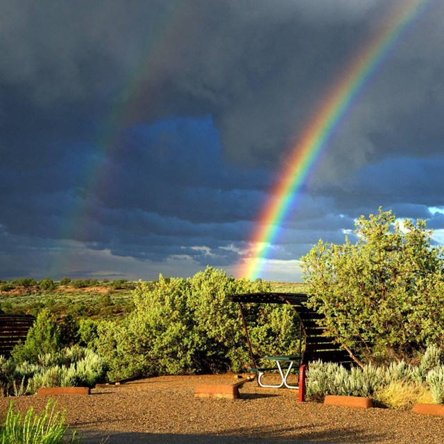 campsite with shade structure underneath a rainbow
