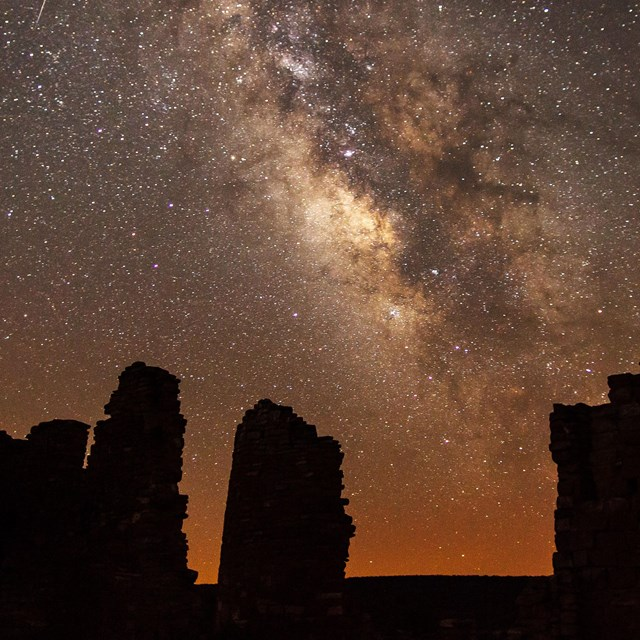silhouetted structures with the night sky and Milky Way overhead.