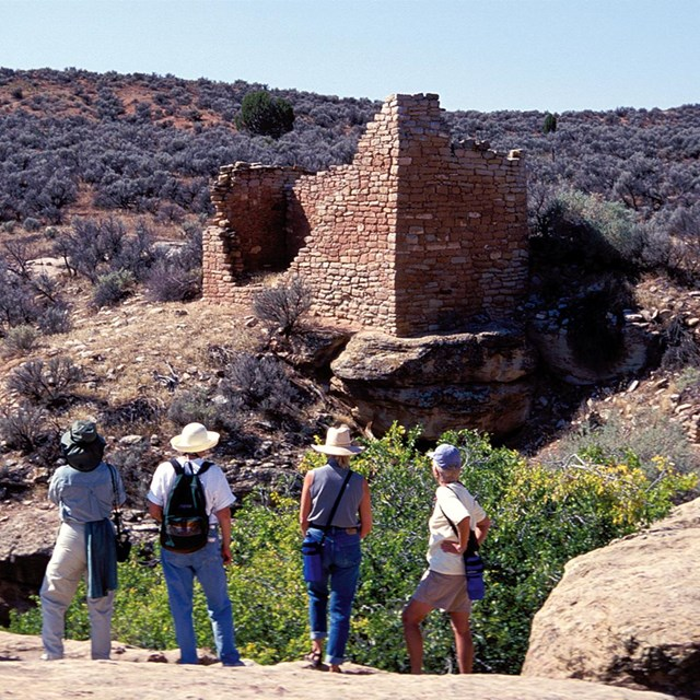 A group of people looking at a rock structure