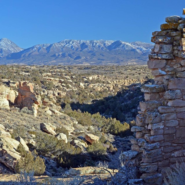 stone structure with canyon and Sleeping Ute Mountain in background