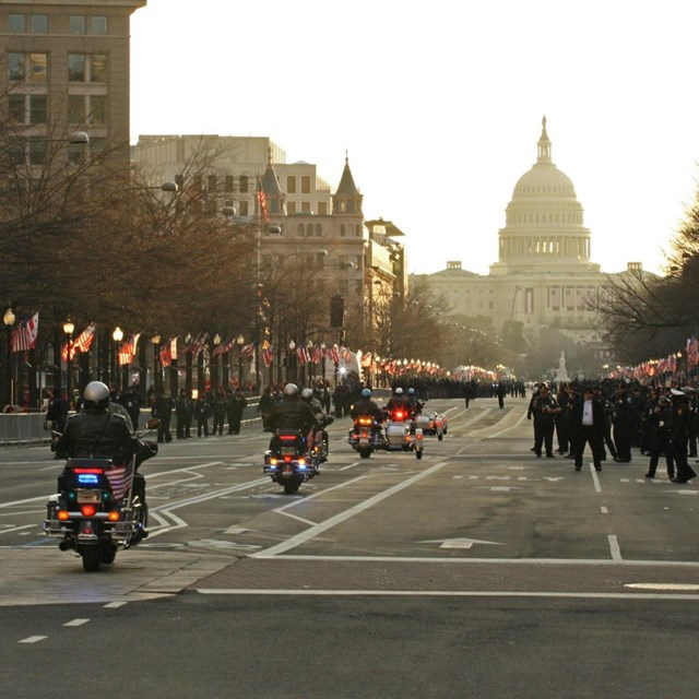 Police on motorcycles riding a  parade route towards the US Capitol building