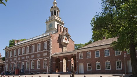 Color photo of Independence Hall, a two story red brick building with many windows and clock tower.