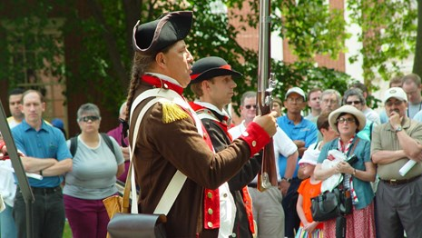 Color photo of people watching two men dressed in 18th century military dress with muskets pass by.