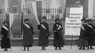 Black and white photo of women suffragists from the early 1900s picketing the White House.