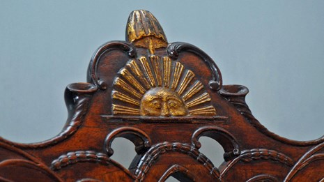 Color photo showing a detail from a chair's crest rail with a carved sun and liberty pole and cap.