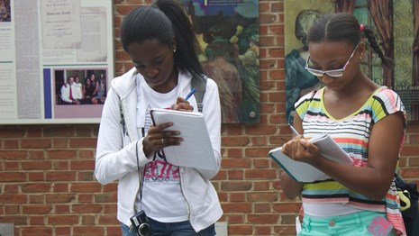 Color photo showing two teen girls standing in an outdoor exhibit area and writing in notebooks.