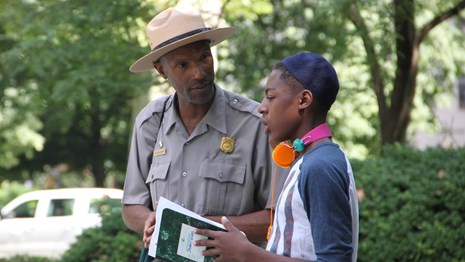 Color image showing a male park ranger and a teenage boy talking in an outdoor setting.