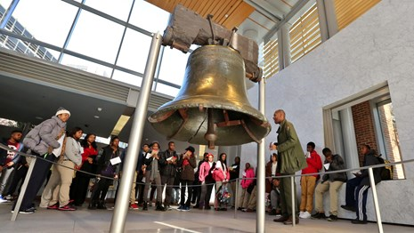 Color photo showing a school group standing around the Liberty Bell.