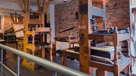 Color photo showing two reproduction 18th century printing presses.