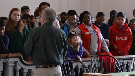 Color photo of a group of students gathered along a banister while a man speaks at Independence Hall