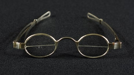 Color photo of 18th century bifocal eyeglasses against a black background.