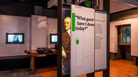 Color photo of an exhibit panel with an image of Benjamin Franklin, and exhibits behind.