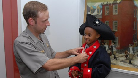 Color photo of a male park ranger helping a boy in tricorner hat button a colonial military coat.
